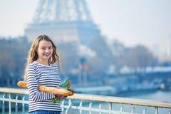 Chica joven hermosa con el baguette y los tulipanes cerca de la torre Eiffel Fotografía de archivo libre de regalías