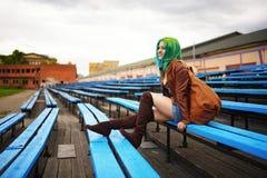 Chica joven hermosa con el bolso que presenta en banco en el estadio de fútbol Imagenes de archivo