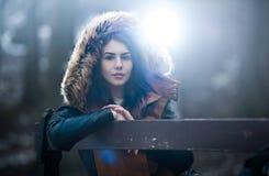 Chica joven hermosa con el cabo marrón de la piel que disfruta del paisaje del invierno que se sienta en el banco en parque Adole Fotos de archivo