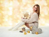 Chica joven hermosa con el juguete del oso de peluche en el fondo amarillo del bokeh - concepto romántico del día de fiesta Fotografía de archivo