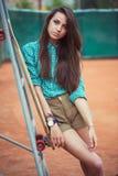 Chica joven hermosa con el longboard que se coloca en el campo de tenis Imagen de archivo libre de regalías