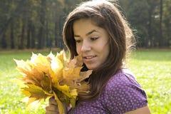 Chica joven hermosa con el manojo de hojas imagenes de archivo