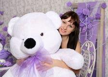 Chica joven hermosa con el oso blanco grande del juguete Foto de archivo