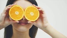 Chica joven hermosa con el pelo largo, la piel perfecta y el maquillaje perfecto Sostenga la fruta anaranjada en el fondo del ojo almacen de video