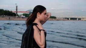 Chica joven hermosa con el pelo oscuro en la playa Luz de la puesta del sol C?mara lenta almacen de metraje de vídeo