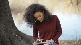 Chica joven hermosa con el pelo rizado oscuro usando la tableta, al aire libre metrajes