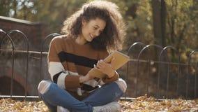 Chica joven hermosa con el pelo rizado oscuro usando la tableta, al aire libre almacen de metraje de vídeo