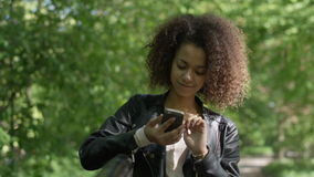 Chica joven hermosa con el pelo rizado oscuro usando su teléfono celular, al aire libre