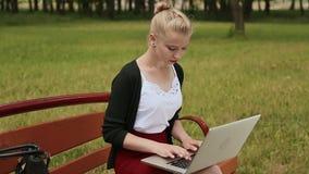 Chica joven hermosa con el pelo rubio en un banco de parque que trabaja en su ordenador portátil Muchacha que usa el ordenador po almacen de video