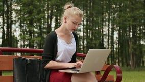 Chica joven hermosa con el pelo rubio en un banco de parque que trabaja en su ordenador portátil Muchacha que usa el ordenador po metrajes