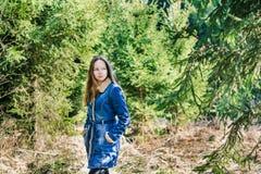 Chica joven hermosa con el pelo rubio largo en una chaqueta azul del dril de algod?n en un bosque verde en un d?a de primavera so fotos de archivo