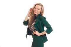Chica joven hermosa con el pelo rubio que sonríe y que presenta para la cámara en un traje verde Imagenes de archivo