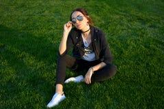 Chica joven hermosa con el rojo-pelo que se sienta en la hierba verde al aire libre Fotografía de archivo libre de regalías