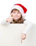 Chica joven hermosa con el sombrero de santa que se coloca detrás del tablero blanco Imagen de archivo