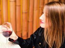 Chica joven hermosa con el vidrio de vino rojo Fotografía de archivo libre de regalías
