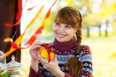 Chica joven hermosa con la caja de regalo a disposición en parque del otoño Feliz Fotografía de archivo libre de regalías