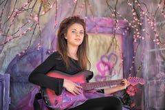 Chica joven hermosa con la guitarra eléctrica Imágenes de archivo libres de regalías