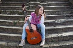 Chica joven hermosa con la guitarra que se sienta en las escaleras y que mira lejos Fotografía de archivo