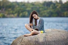 Chica joven hermosa con la manzana que lee un libro foto de archivo