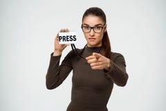 Chica joven hermosa con la placa de prensa a disposición que señala en la cámara Sobre el fondo blanco Fotografía de archivo