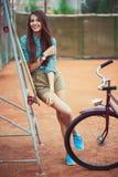 Chica joven hermosa con la situación del longboard y de la bicicleta Fotos de archivo