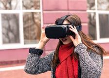 Chica joven hermosa con las auriculares de la realidad virtual o los vidrios 3d Imagenes de archivo