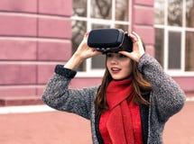 Chica joven hermosa con las auriculares de la realidad virtual o los vidrios 3d Fotos de archivo