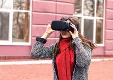 Chica joven hermosa con las auriculares de la realidad virtual o los vidrios 3d Fotografía de archivo libre de regalías