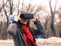 Chica joven hermosa con las auriculares de la realidad virtual o los vidrios 3d Foto de archivo