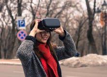 Chica joven hermosa con las auriculares de la realidad virtual o los vidrios 3d Foto de archivo libre de regalías