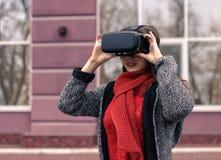 Chica joven hermosa con las auriculares de la realidad virtual o los vidrios 3d Fotos de archivo libres de regalías