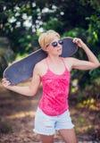 Chica joven hermosa con las gafas de sol que llevan del tablero del patín Imagen de archivo