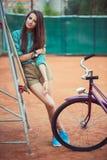 Chica joven hermosa con longboard y bicicleta que se coloca en Imagen de archivo libre de regalías