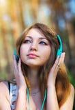Chica joven hermosa con los auriculares Imagenes de archivo