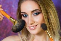 Chica joven hermosa con los ojos azules que presentan con las borlas Fotos de archivo