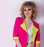 Chica joven hermosa con los ojos brillantes, pelo liso en una chaqueta rosada brillante, estudio de la fotografía de la moda Foto de archivo