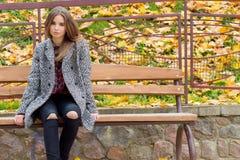 Chica joven hermosa con los ojos tristes del otoño grande en una capa y vaqueros negros rasgados que se sientan en un banco en pa Imagen de archivo libre de regalías