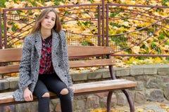 Chica joven hermosa con los ojos tristes del otoño grande en una capa y vaqueros negros rasgados que se sientan en un banco en pa Foto de archivo