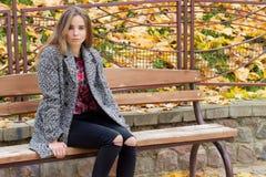 Chica joven hermosa con los ojos tristes del otoño grande en una capa y vaqueros negros rasgados que se sientan en un banco en pa Fotografía de archivo