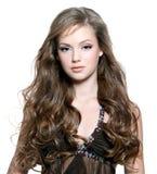 Chica joven hermosa con los pelos rizados largos fotografía de archivo libre de regalías