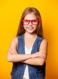 Chica joven hermosa con los vidrios rojos Foto de archivo libre de regalías