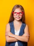 Chica joven hermosa con los vidrios rojos Imagen de archivo libre de regalías