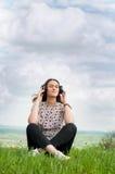 Chica joven hermosa con música al aire libre que escucha de los auriculares Imágenes de archivo libres de regalías
