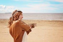 Chica joven hermosa con un aeroplano del juguete en la orilla de la bahía en la ropa del piloto, espacio de la copia Fotos de archivo libres de regalías