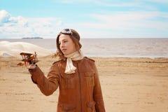 Chica joven hermosa con un aeroplano del juguete en su mano en la orilla de la bahía en la ropa del piloto, espacio de la copia Imagen de archivo