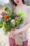 Chica joven hermosa con un ramo de flores Imágenes de archivo libres de regalías