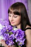 Chica joven hermosa con un ramo de flores púrpuras Fotos de archivo