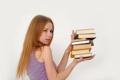 Chica joven hermosa con una pila de libros Fotografía de archivo libre de regalías