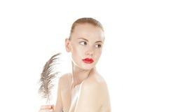 Chica joven hermosa con una pluma de la avestruz. Imagen de archivo libre de regalías