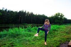 Chica joven hermosa contratada a aptitud en naturaleza Fondo Imagen de archivo